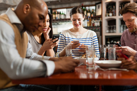 check out: Friends at restaurant texting and showing photos using cell phones LANG_EVOIMAGES