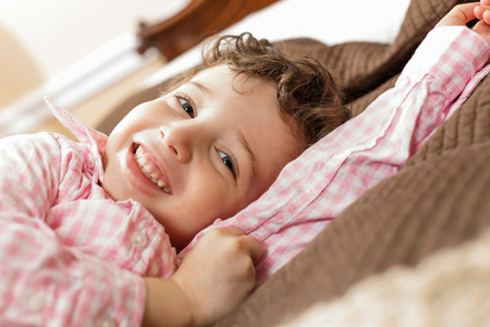 off shoulder: Smiling boy laying on bed