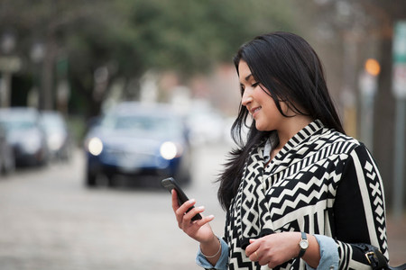 multi tasking: Young woman holding cell phone