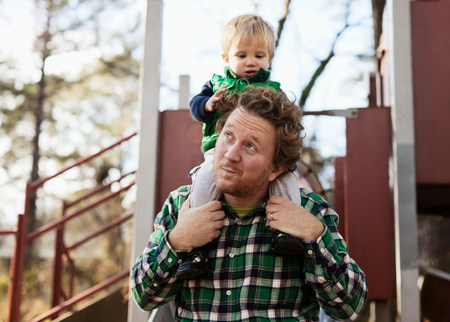 off shoulder: Father carrying son on shoulders in park