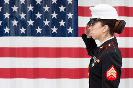 Servicewoman in dress blues by US flag LANG_EVOIMAGES