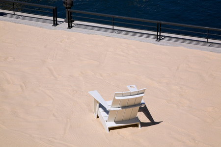 travel features: Lawn chair in sand on urban beach LANG_EVOIMAGES
