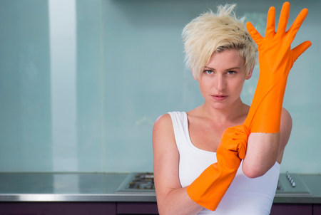 Young woman putting on orange washing up gloves