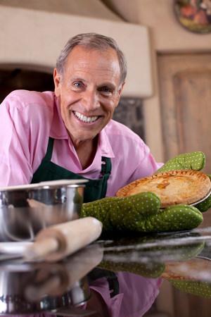sultry: Older man holding pie in kitchen
