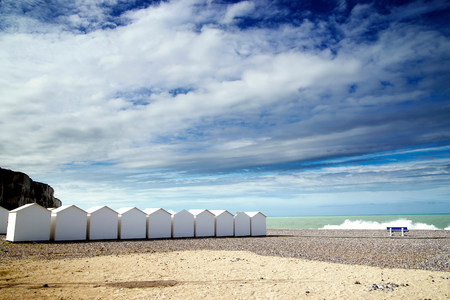 vacant land: White beach huts in a row on shingle beach LANG_EVOIMAGES