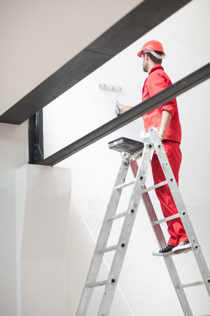 coveralls: Decorator on ladder painting interior wall