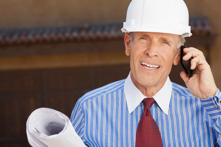 Businessman in hard hat with blueprints