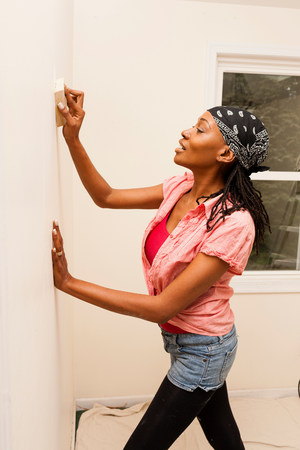 matures: Woman priming wall in new home
