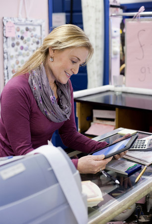 information superhighway: Cashier using tablet computer in store