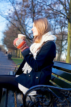 daydream: Woman having coffee on park bench