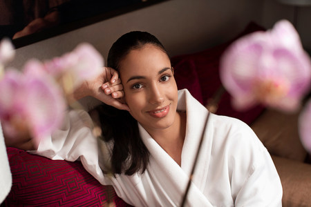 above 18: Woman in bathrobe sitting on sofa LANG_EVOIMAGES