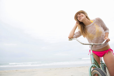 travel features: Woman on bicycle on beach