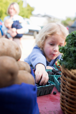 nourishing: Boy eating fruit at farmers market LANG_EVOIMAGES
