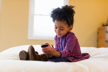 Girl playing with cell phone on bed