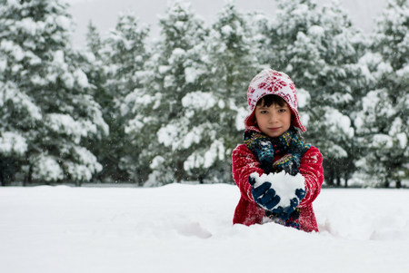 Boy holding snowball outdoors