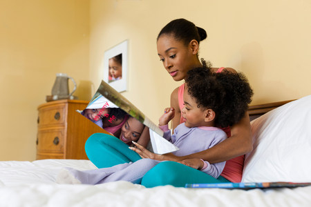Mother and daughter reading on bed LANG_EVOIMAGES