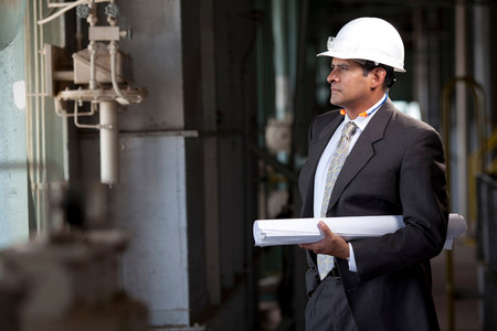 Businessman with blueprints in plant