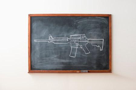 dangerous ideas: Chalk drawing of gun on blackboard