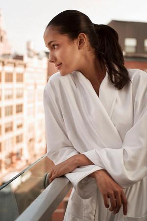 mornings: Woman wearing bathrobe on balcony LANG_EVOIMAGES