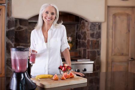 low self esteem: Older woman making smoothie in kitchen LANG_EVOIMAGES