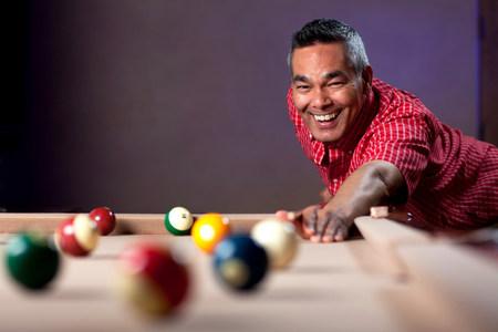 pool cues: Smiling man playing pool LANG_EVOIMAGES