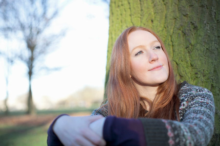 hopefulness: Woman sitting by tree outdoors