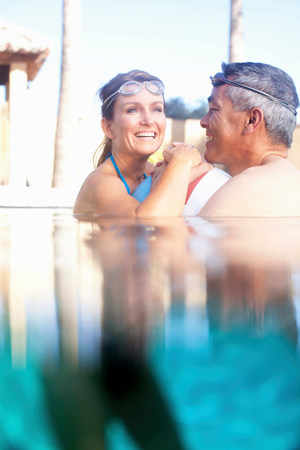 Couple swimming together in pool LANG_EVOIMAGES