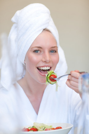 Young woman wearing towel on head eating salad LANG_EVOIMAGES
