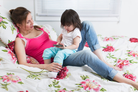 information superhighway: Portrait of pregnant woman and toddler daughter lounging on bed with smartphone