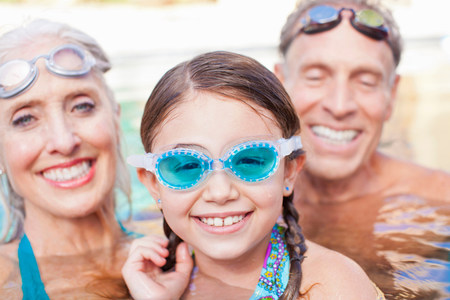Girl and grandparents swimming in pool LANG_EVOIMAGES