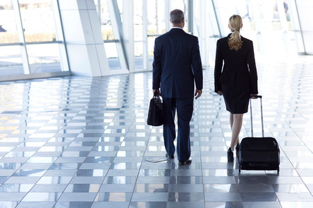 45 50: Businesspeople walking through airport with suitcases LANG_EVOIMAGES