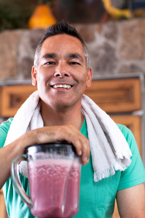 Man making smoothie in kitchen