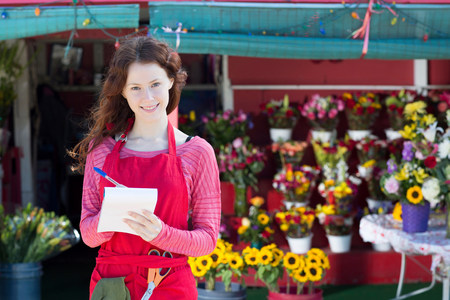 Florist making notes in shop