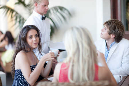 cup four: Young adults in restaurant with waiter LANG_EVOIMAGES