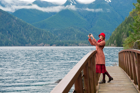 Woman taking picture on wooden bridge