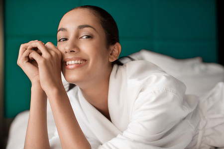 Woman in bathrobe smiling on bed LANG_EVOIMAGES