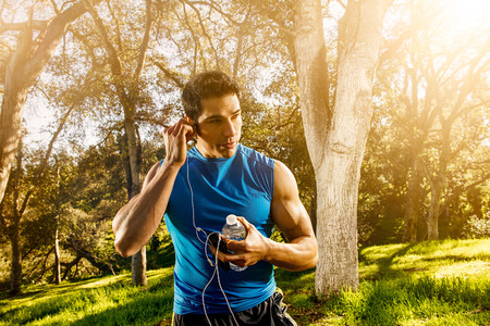 Young man exercising in forest wearing earphones LANG_EVOIMAGES