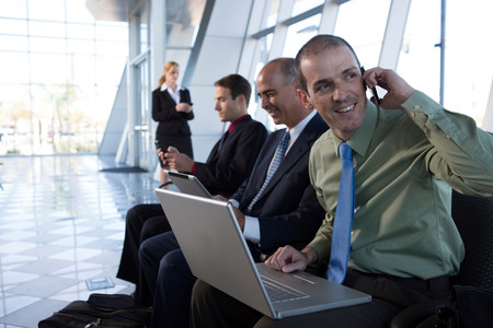 Businessman on cell phone using laptop LANG_EVOIMAGES
