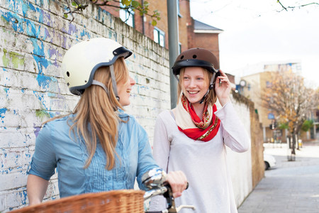 headshots: Women on bicycles on city street LANG_EVOIMAGES