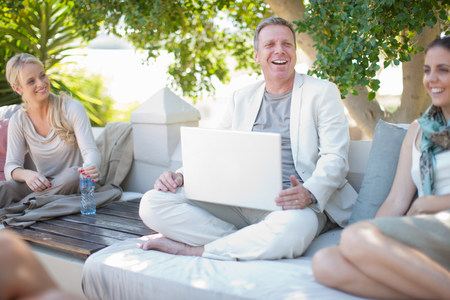 3 year old: Casual business people on patio using laptop