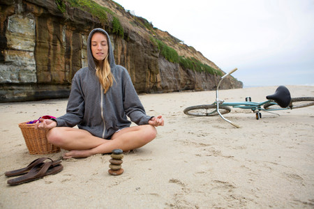 Woman meditating with rocks on beach LANG_EVOIMAGES