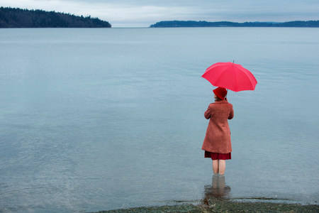 Woman with umbrella in rural lake LANG_EVOIMAGES
