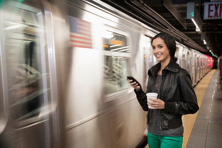 check out: Woman using cell phone at subway station