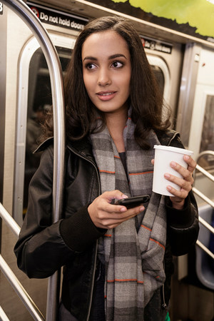 Woman using cell phone on subway