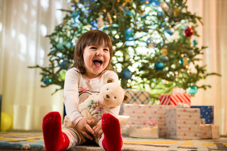 Girl laughing by Christmas tree LANG_EVOIMAGES