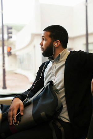 ponderous: Young man traveling on light train wearing earphones LANG_EVOIMAGES