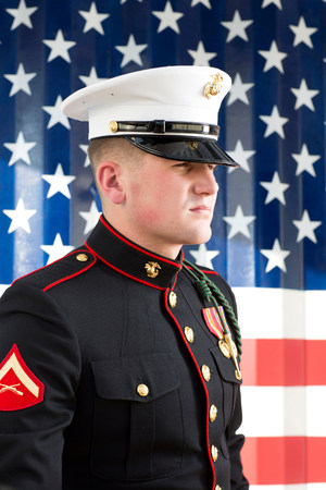 Serviceman in dress blues by US flag LANG_EVOIMAGES
