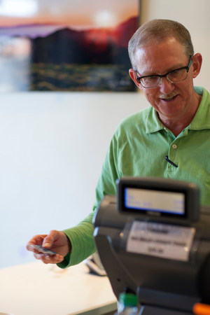 cash register building: Cashier running credit card in store