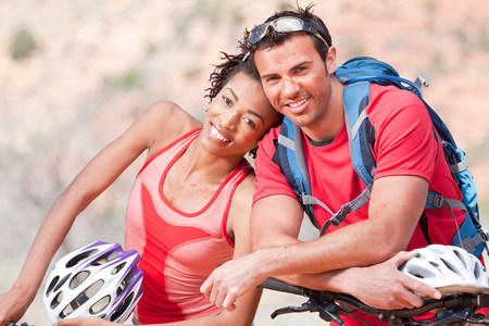 Couple smiling on mountain bikes LANG_EVOIMAGES