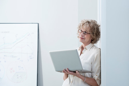 information superhighway: Businesswoman using laptop in office LANG_EVOIMAGES